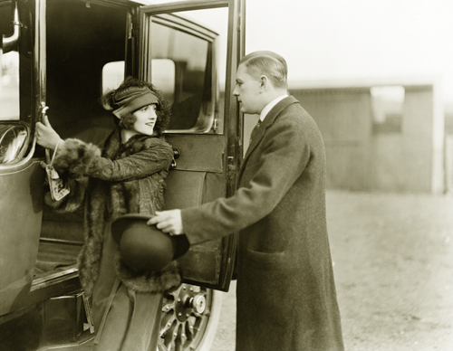 man helping woman get into an old fashioned car
